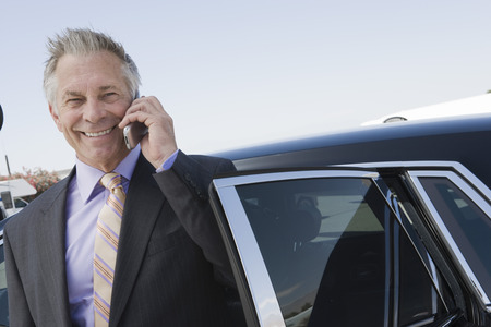 Portrait of senior businessman standing in front of limousine and talking on phone. Stock Photo - 5475008