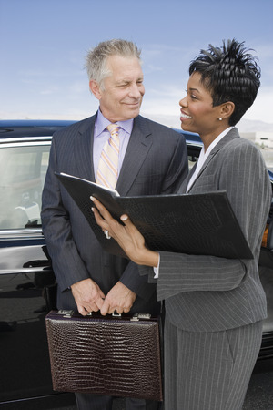 Senior businessman with mid-adult businesswoman standing in front of car. Stock Photo - 5475009