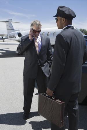 シニア ・ ビジネスマン立って外のプライベート ジェットと運転手彼のスーツケースを持って、携帯電話で話しています。 写真素材