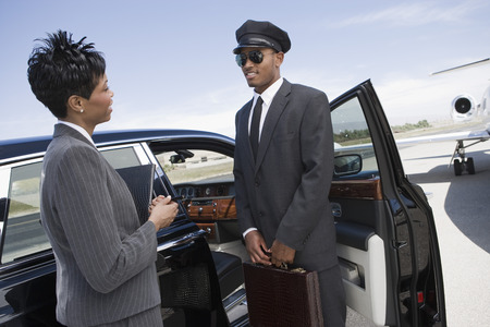 ミッド アダルト ビジネスウーマンと半ば大人運転手付きのリムジンの前に立っていると話しています。 写真素材