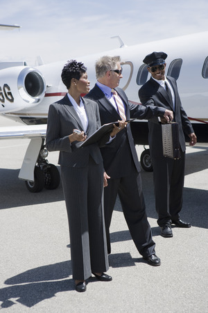 Senior businessman, mid-adult businesswoman and airline pilot in front of private jet. Stock Photo - 5475013