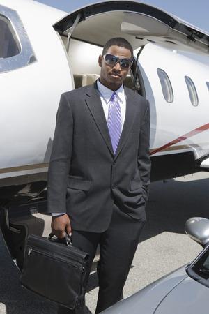 アフリカ系アメリカ人の実業家プライベート飛行機や車の前に立っています。