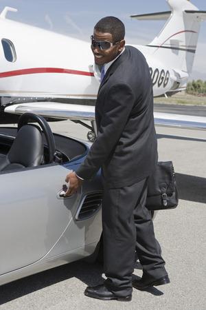 アフリカ系アメリカ人実業家ランディング ストリップ上のコンバーチブルのドアを開ける。 写真素材