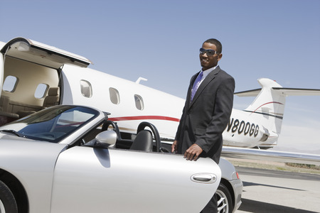 African-American businessman opening door of convertible on landing strip. Stock Photo - 5475017