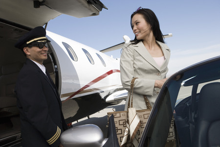 Mid-adult businesswoman turning back on pilot and smiling. Stock Photo - 5475020