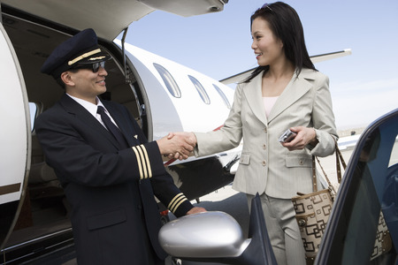 Mid-adult businesswoman shaking hands with pilot outside of private jet. Stock Photo - 5475021