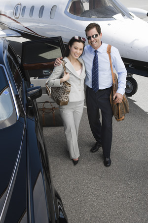 Businesswoman and businessman standing in front of airplane and embracing, elevated view. Stock Photo - 5475025