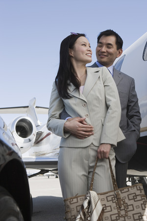 Mid-adult Asian business couple standing in front of car and airplane. Stock Photo - 5475037