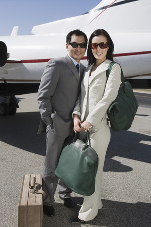 Portrait of mid-adult Asian business couple standing outside of private airplane. Stock Photo - 5475039