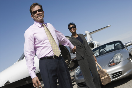Mid-adult  business couple outside of car and airplane.