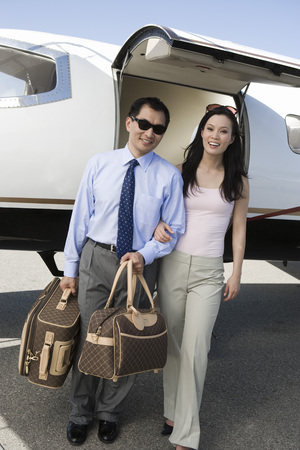 private airplane: Portrait of mid-adult Asian business couple standing in front of private airplane.