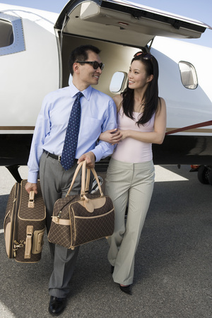 private airplane: Mid-adult Asian business couple walking in front of private airplane.