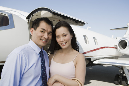 Portrait of mid-adult Asian business couple standing in front of private airplane. Stock Photo - 5475043