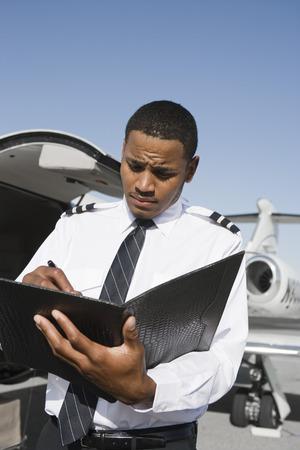 立っていると、飛行機の前にノートを作る航空会社のパイロット。