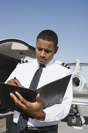 airline pilot: Airline pilot standing and making notes in front of airplane.