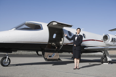 Female flight attendant standing in front of private jet on runway. Stock Photo - 5475047