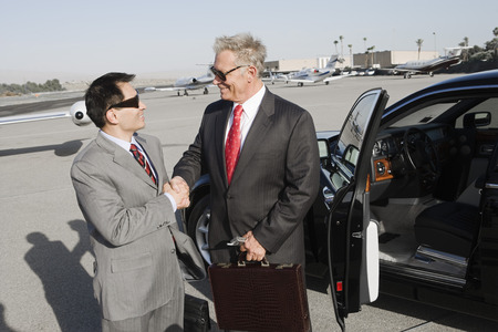 landing strip: Two businessmen standing on landing strip in front of car and shaking hands.