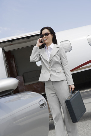 Mid-adult businesswoman using mobile phone in front of airplane and car. Stock Photo - 5475058