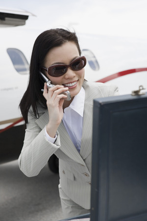 Mid-adult businesswoman using mobile phone outside of airplane. Stock Photo - 5475059