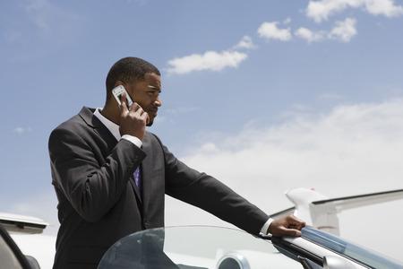 半ば大人ビジネスマン コンバーチブルに立って、携帯電話を使用して。 写真素材