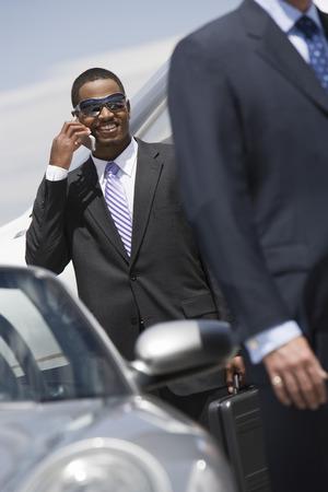 半ば大人のビジネスマンは車の外の携帯電話を使用して。