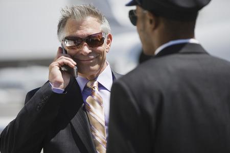シニアのビジネスマンは彼の運転手は彼を支援、携帯電話で話しています。 写真素材