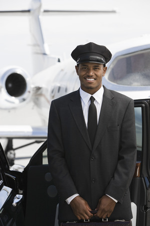 car driver: Portrait of mid-adult chauffeur standing in front of limousine and private jet.