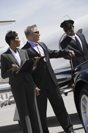 Mid-adult businesswoman, senior businessman and chauffeur in front of car. Stock Photo - 5475072