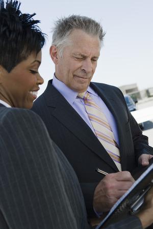 businessman signing documents: Senior businessman signing documents.
