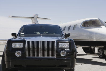 Limousine and private jet on landing strip. LANG_EVOIMAGES