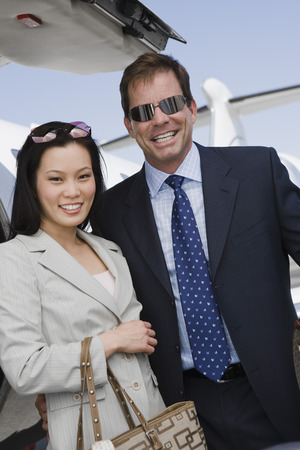 Mid-adult businesswoman and businessman standing in front of airplane. Stock Photo - 5475077