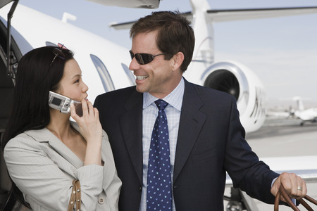 Mid-adult businesswoman and businessman flirting in front of airplane. Stock Photo - 5475078