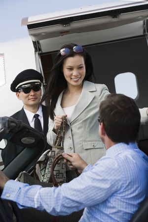Mid-adult businesswoman getting out of airplane, two men assisting. Banque d'images - 5475079