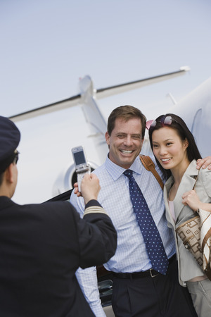 Airline pilot taking picture of businesswoman and businessman with mobile phone. Stock Photo - 5475080