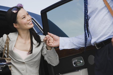 Mid-adult businesswoman getting of car, man assisting. Stock Photo - 5475081
