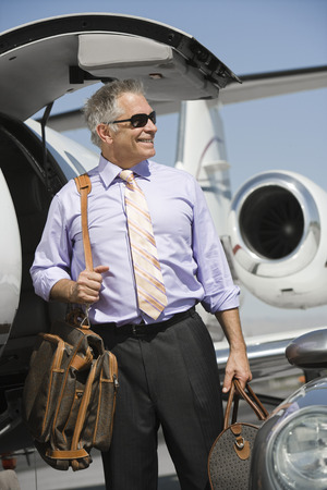 shades of grey: Senior businessman in front of private jet.