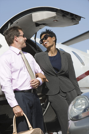Mid-adult businesswoman and businessman getting of airplane. Stock Photo - 5475088