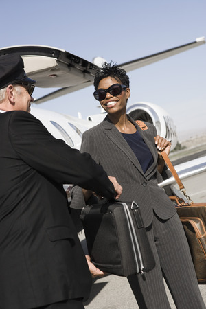 Mid-adult businesswoman giving suitcase to chauffeur in front of airplane Stock Photo - 5475089