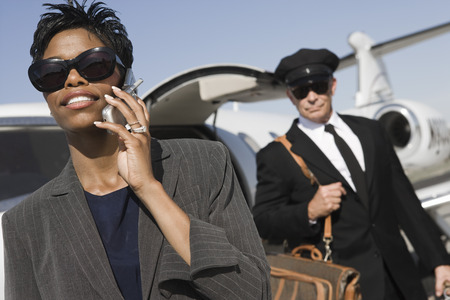Mid-adult businesswoman talking on phone while chauffeur is waiting Stock Photo - 5475090