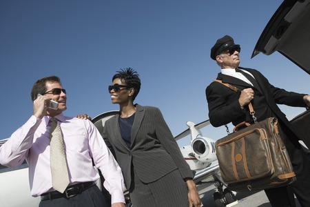 ミッド アダルト ビジネスウーマン、ビジネスマンおよび運転者を前に滑走路に飛行機のビュー角度を低します。 写真素材