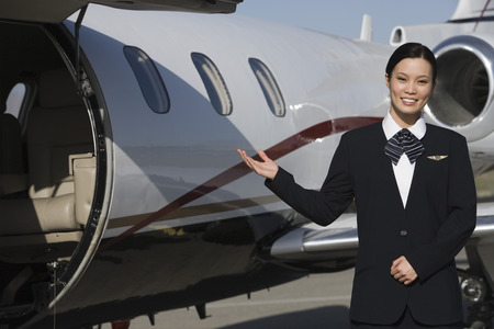 Female Asian mid-adult flight attendant in front of private jet. Stock Photo - 5475095