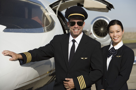 airline uniform: Portrait of mid-adult airline pilot and flight attendant in front of  airplane.