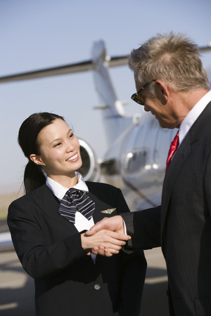 Mid-adult flight attendant and senior businessman shaking hands. Stock Photo - 5475097