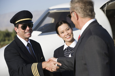Mid-adult airline pilot and senior businessman shaking hands. Stock Photo - 5475098