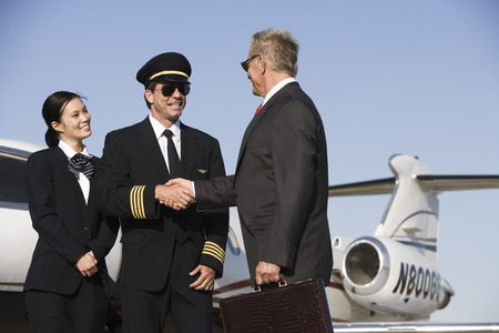 Mid-adult airline pilot and senior businessman shaking hands. Stock Photo - 5475099
