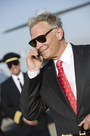 Mid-adult businessman talking on phone, airline pilot standing in background. Stock Photo - 5475100