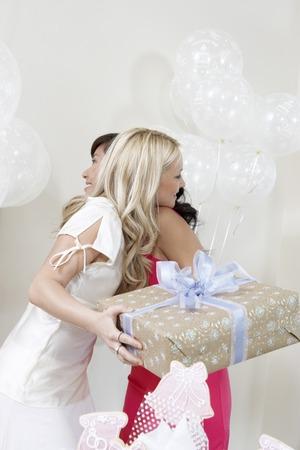 wedding customs: Friends Hugging at Bridal Shower LANG_EVOIMAGES