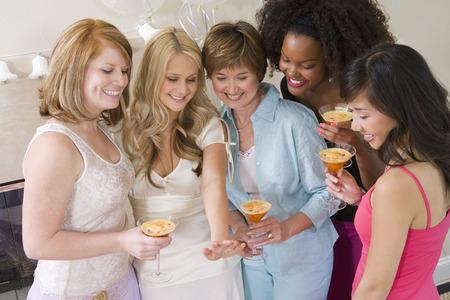 花嫁は彼女の婚約指輪を見て友人と一緒に立っています。