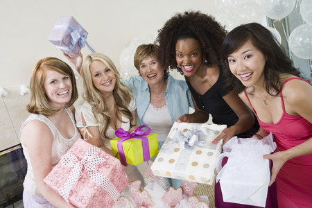 customs and celebrations: Friends standing Together holding gifts at Bridal Shower