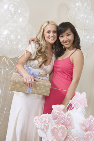 Bride and Friend standing Together holding gift at Bridal Shower Stock Photo - 5475141